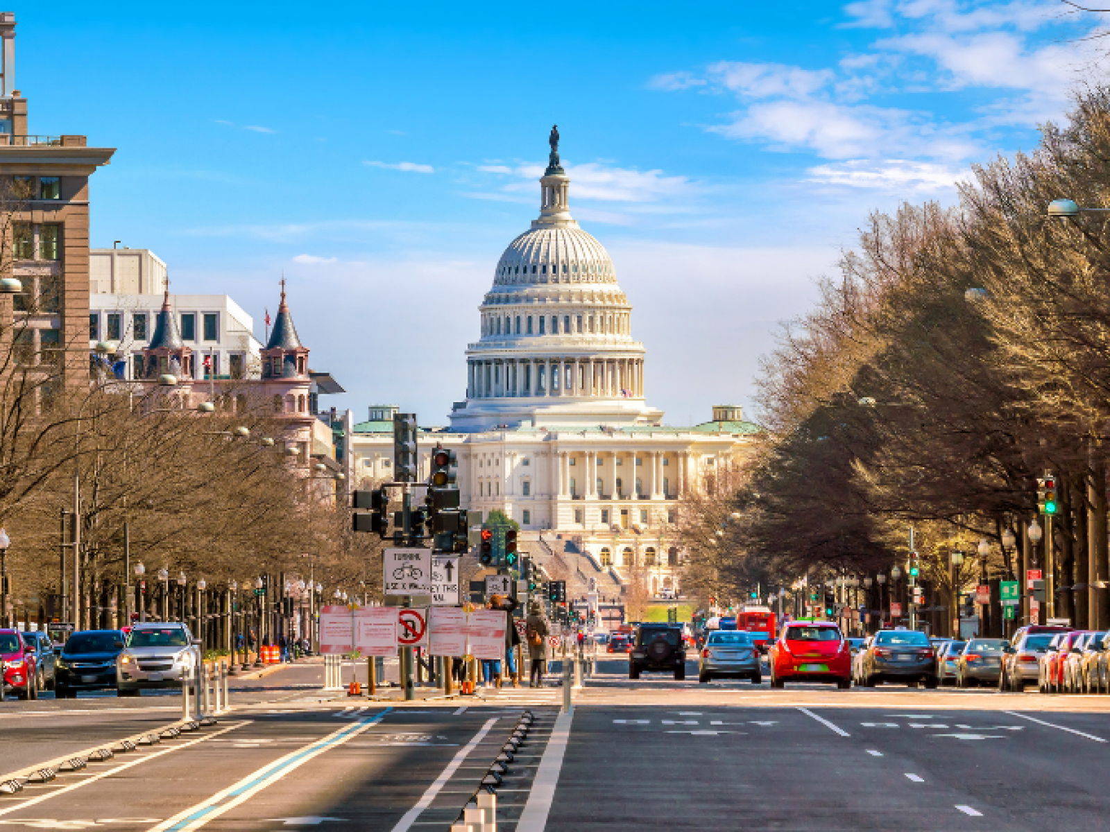 Photo of busy street with United States Capitol in the background